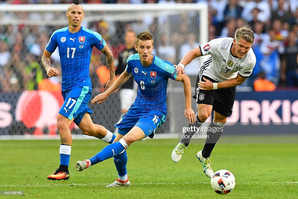 Germany's midfielder Bastian Schweinsteiger (R) challenges Slovakia's midfielder Jan Gregus during the Euro 2016 round of 16 football match between Germany and Slovakia at the Pierre-Mauroy stadium in Villeneuve-d'Ascq near Lille on June 26, 2016. / AFP / Joe KLAMAR