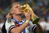 Germany's midfielder Bastian Schweinsteiger kisses the World Cup trophy as his team celebrate winning the 2014 FIFA World Cup final football match...