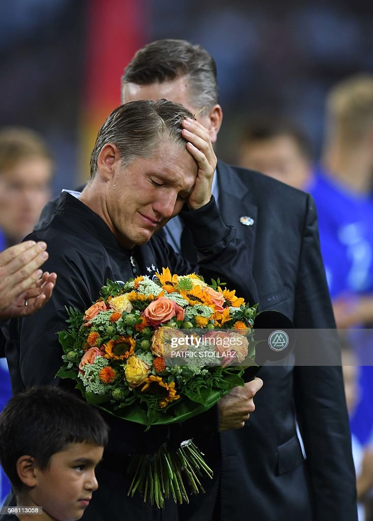 TOPSHOT - Germany's midfielder Bastian Schweinsteiger reacts during the ceremony marking his last match for his country prior to the football friendly match between Germany and Finland in Monchengladbach, western Germany on on August 31, 2016. STOLLARZ