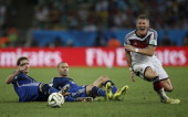 Germany's midfielder Bastian Schweinsteiger vies with Argentina's midfielder Lucas Biglia and Argentina's midfielder Javier Mascherano during the...