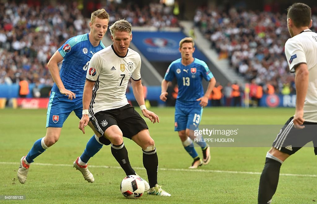 Germany's midfielder Bastian Schweinsteiger (C) vies with Slovakia's midfielder Jan Gregus during the Euro 2016 round of 16 football match between Germany and Slovakia at the Pierre-Mauroy stadium in Villeneuve-d'Ascq, near Lille, on June 26, 2016. / AFP / PHILIPPE