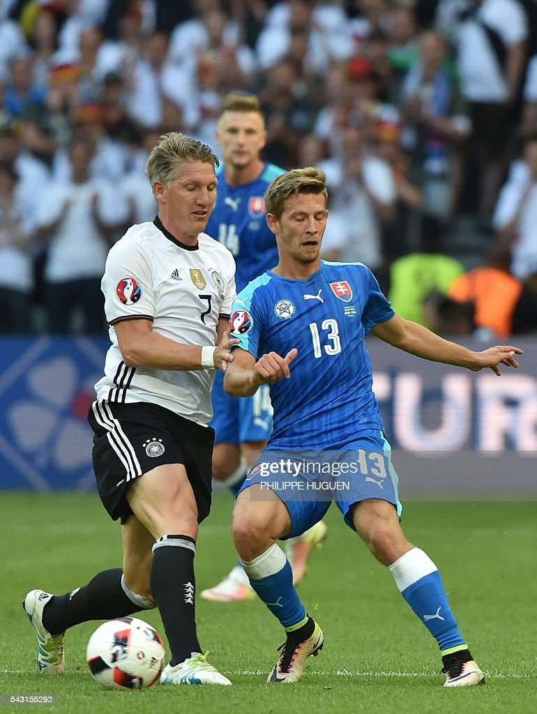 Germany's midfielder Bastian Schweinsteiger vies with Slovakia's midfielder Patrik Hrosovsky during the Euro 2016 round of 16 football match between Germany and Slovakia at the Pierre-Mauroy stadium in Villeneuve-d'Ascq, near Lille, on June 26, 2016. / AFP / PHILIPPE