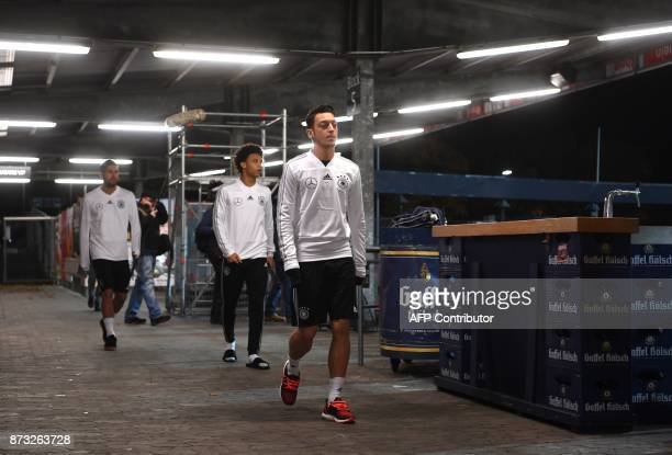 Germany's midfielder Emre Can Germany's midfielder Leroy Sane and Germany's midfielder Mesut Oezil arrive at a training session ahead of their...