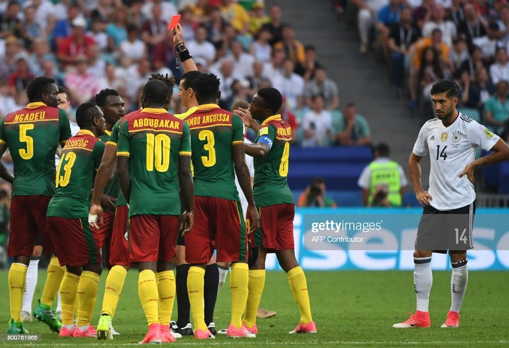 Germany's midfielder Emre Can reacts as Colombian referee Wilmar Roldan (C) gives a red card to Cameroon's defender Ernest Mabouka during the 2017 FIFA Confederations Cup group B football match between Germany and Cameroon at the Fisht Stadium Stadium in Sochi on June 25, 2017. / AFP PHOTO / Patrik STOLLARZ