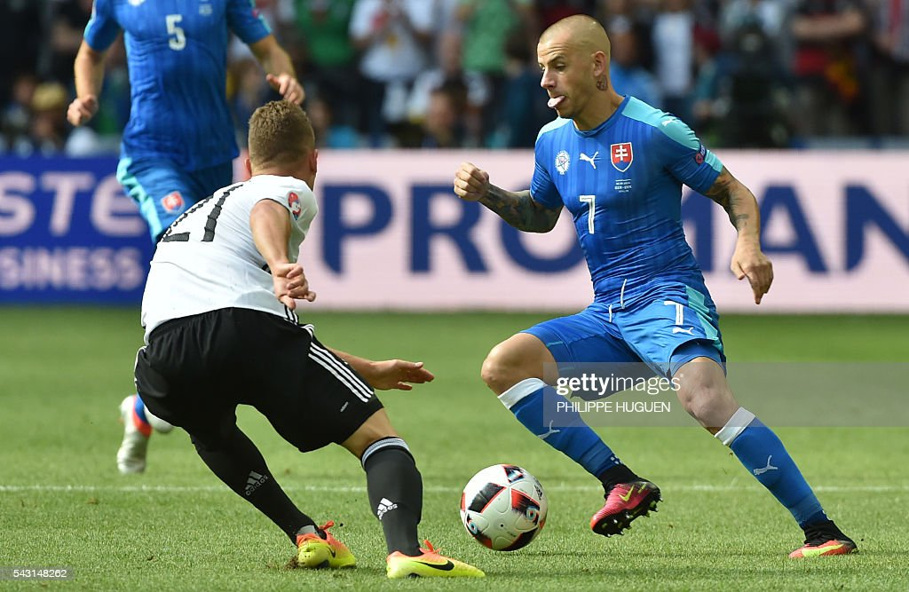 Germany's midfielder Joshua Kimmich (L) vies with Slovakia's midfielder Vladimir Weiss during the Euro 2016 round of 16 football match between Germany and Slovakia at the Pierre-Mauroy stadium in Villeneuve-d'Ascq, near Lille, on June 26, 2016. / AFP / PHILIPPE