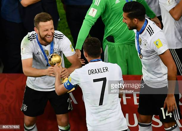 Germany's midfielder Julian Draxler and Germany's defender Shkodran Mustafi celebrate with the trophy after winning the 2017 Confederations Cup final...