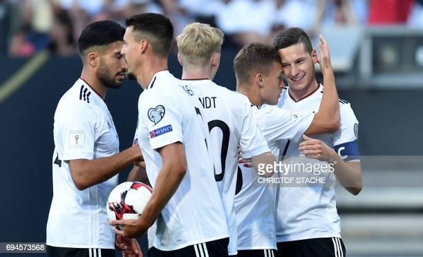Germany's midfielder Julian Draxler celebrates scoring the opening goal with his teammates midfielder Emre Can midfielder Sandro Wagner midfielder...