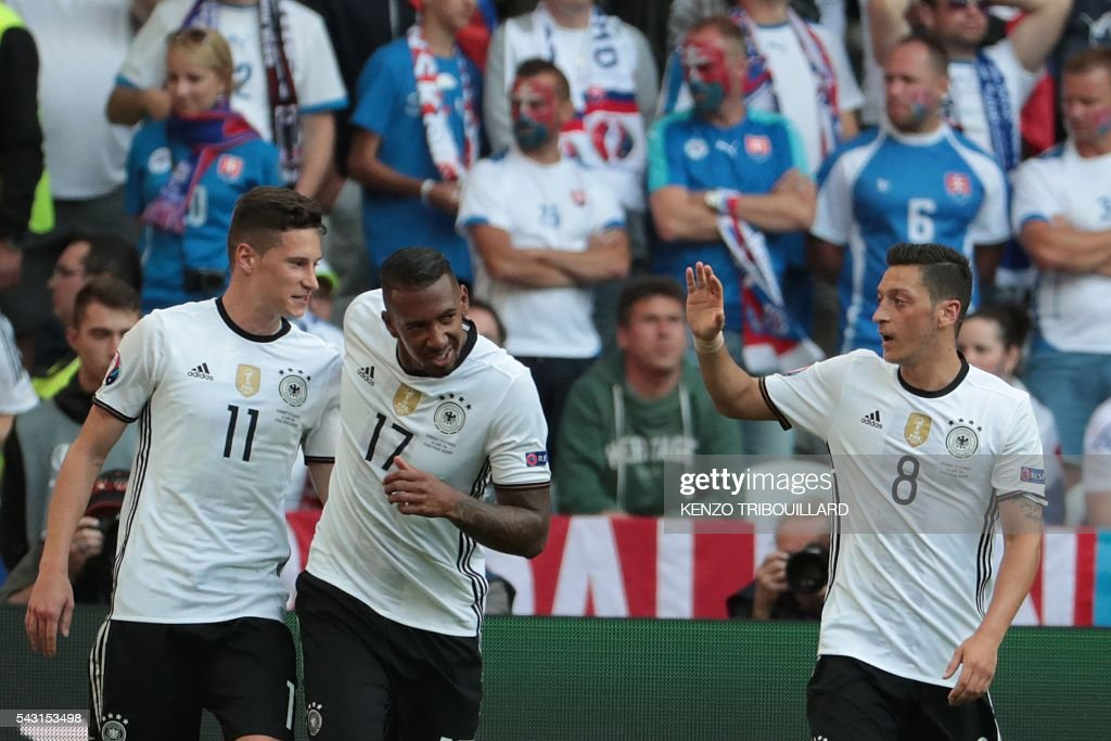 Germany's midfielder Julian Draxler (L) celebrates with Germany's defender Jerome Boateng and Germany's midfielder Mesut Oezil (R) after scoring his team's third goal during the Euro 2016 round of 16 football match between Germany and Slovakia at the Pierre-Mauroy stadium in Villeneuve-d'Ascq near Lille on June 26, 2016. / AFP / KENZO