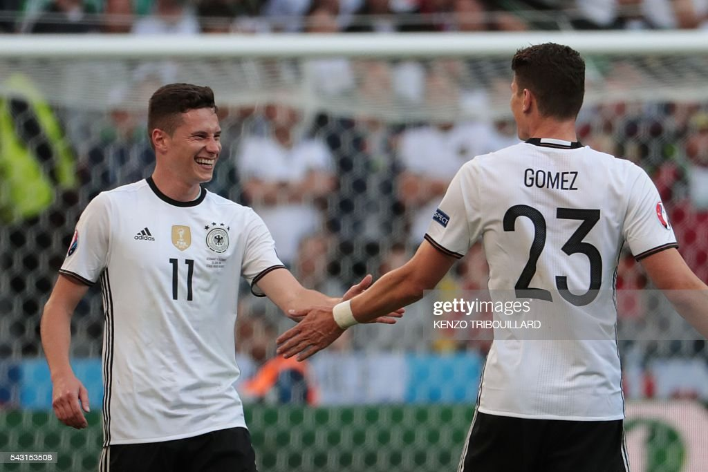 Germany's midfielder Julian Draxler (L) celebrates with Germany's forward Mario Gomez after scoring their third goal during the Euro 2016 round of 16 football match between Germany and Slovakia at the Pierre-Mauroy stadium in Villeneuve-d'Ascq near Lille on June 26, 2016. / AFP / KENZO