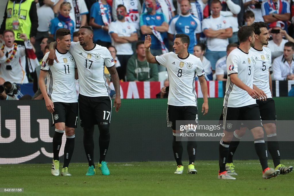 Germany's midfielder Julian Draxler (L) celebrates with teammates after scoring their third goal during the Euro 2016 round of 16 football match between Germany and Slovakia at the Pierre-Mauroy stadium in Villeneuve-d'Ascq near Lille on June 26, 2016. / AFP / KENZO