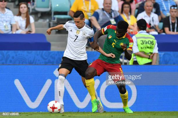 Germany's midfielder Julian Draxler challenges Cameroon's defender Michael NgadeuNgadjui during the 2017 FIFA Confederations Cup group B football...