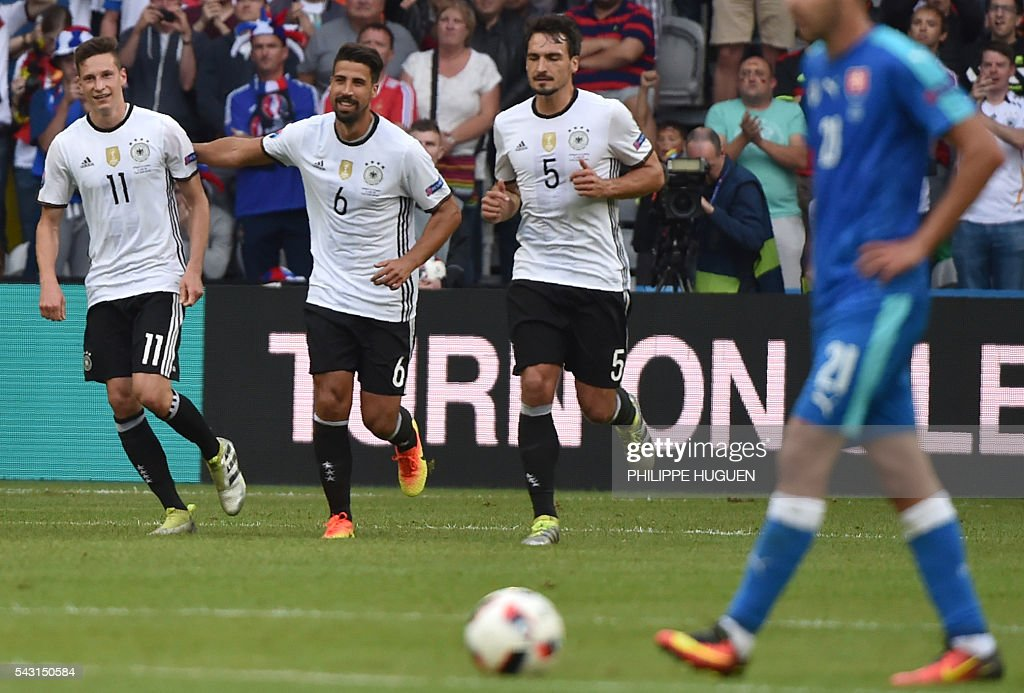 Germany's midfielder Julian Draxler, Germany's midfielder Sami Khedira and Germany's defender Mats Hummels celebrate after Germany's forward Mario Gomez scpred during the Euro 2016 round of 16 football match between Germany and Slovakia at the Pierre-Mauroy stadium in Villeneuve-d'Ascq, near Lille, on June 26, 2016. / AFP / PHILIPPE