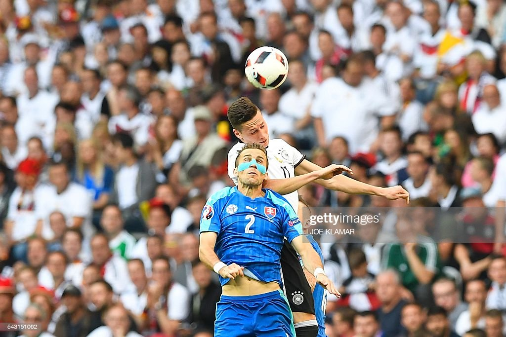 Germany's midfielder Julian Draxler heads the ball behind Slovakia's defender Peter Pekarik during the Euro 2016 round of 16 football match between Germany and Slovakia at the Pierre-Mauroy stadium in Villeneuve-d'Ascq near Lille on June 26, 2016. / AFP / Joe KLAMAR