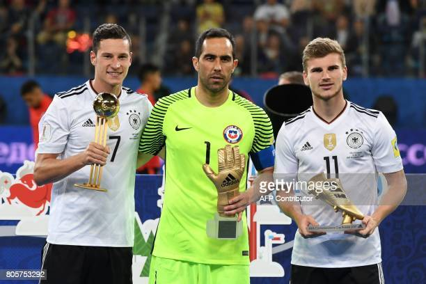 Germany's midfielder Julian Draxler holds the Golden Ball trophy along side Chile's goalkeeper Claudio Bravo holding the Golden Glove trophy and...