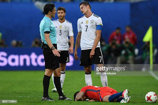 Germany's midfielder Julian Draxler reacts as Chile's midfielder Charles Aranguiz lies on the pitch during the 2017 Confederations Cup final football...
