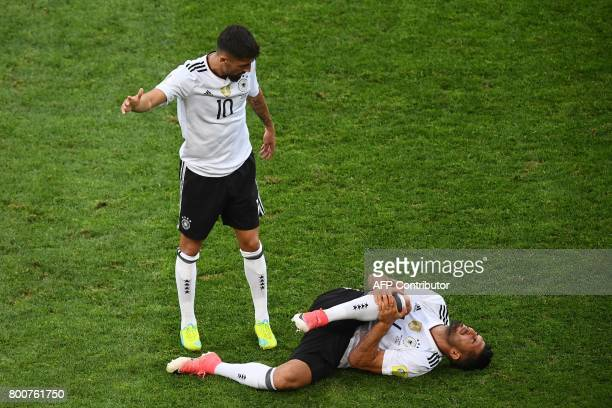 Germany's midfielder Kerem Demirbay calls a medical team as Germany's midfielder Emre Can reacts in pain after a foul during the 2017 FIFA...