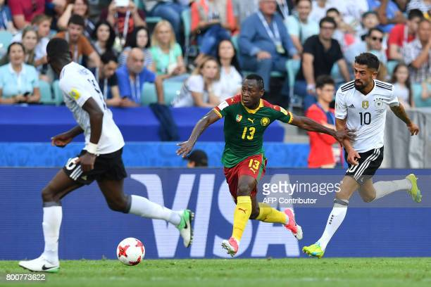 Germany's midfielder Kerem Demirbay challenges Cameroon's forward Christian Bassogog during the 2017 FIFA Confederations Cup group B football match...