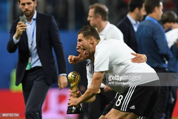 Germany's midfielder Leon Goretzka holds the winner's trophy with defender Joshua Kimmich after they beat Chile 10 in the 2017 Confederations Cup...