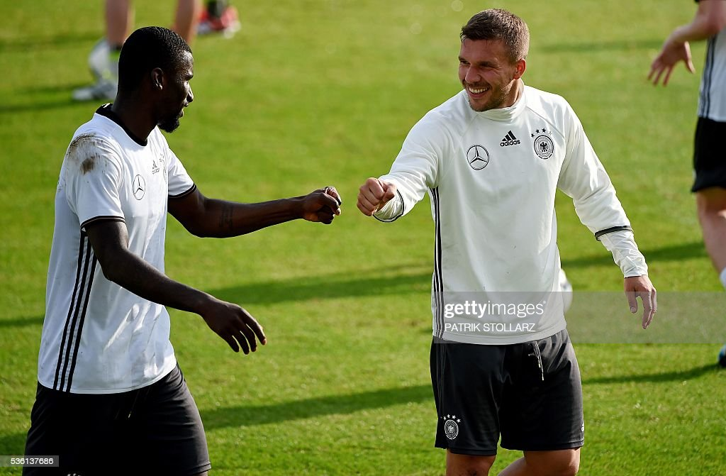 Germany's midfielder Lukas Podolski (R) fist bumps with Germany's defender Antonio Ruediger during a training session on May 31, 2016 in Ascona as part of the team's preparation for the upcoming Euro 2016 European football championships. / AFP / PATRIK