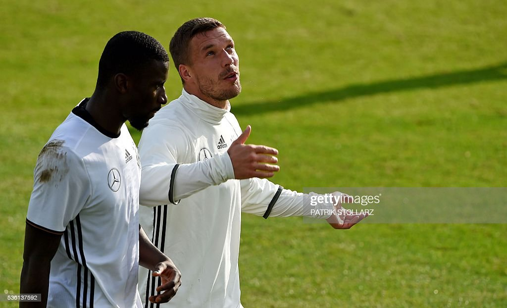 Germany's midfielder Lukas Podolski (R) speaks with Germany's defender Antonio Ruediger during a training session on May 31, 2016 in Ascona as part of the team's preparation for the upcoming Euro 2016 European football championships. / AFP / PATRIK