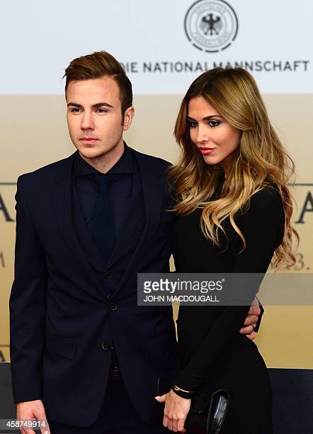 Germany's midfielder Mario Goetze and his girlfriend AnnKathrin Broemmel arrive for a premiere screening of a documentary 'Die Mannschaft' the...