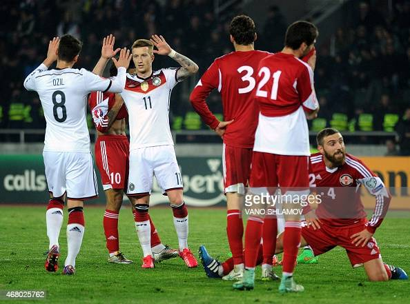 Germany's midfielder Mesut Oezil and Germany's midfielder Marco Reus celebrate their team's second goal during the Euro 2016 qualifying football...