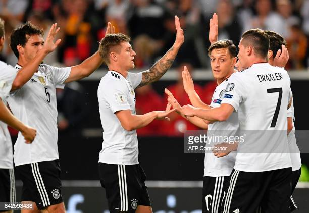 Germany's midfielder Mesut Oezil celebrates with teammates after scoring the opening goal during the FIFA World Cup 2018 qualification match between...