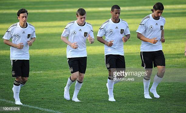 Germany's midfielder Mesut Oezil midfielder Toni Kroos defender Dennis Aogo and midfielder Sami Khedira warm up for a training match Germany vs Sued...