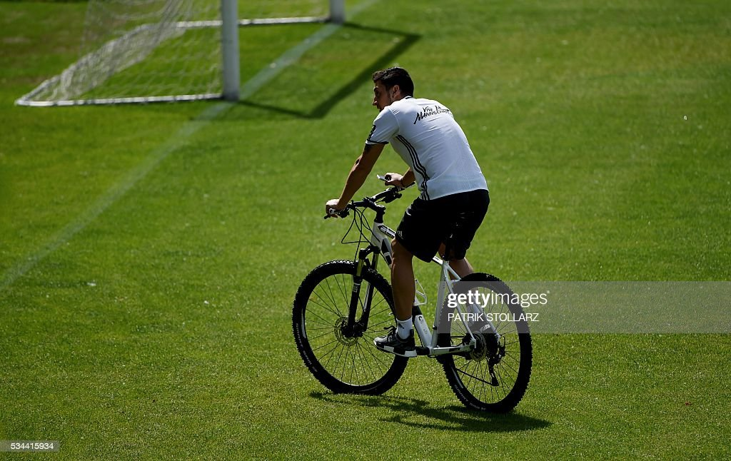 Germany's midfielder Mesut Oezil rides a bike during a training session as part of the team's preparation for the upcoming Euro 2016 European football championships, on May 26, 2016 in Ascona. / AFP / PATRIK