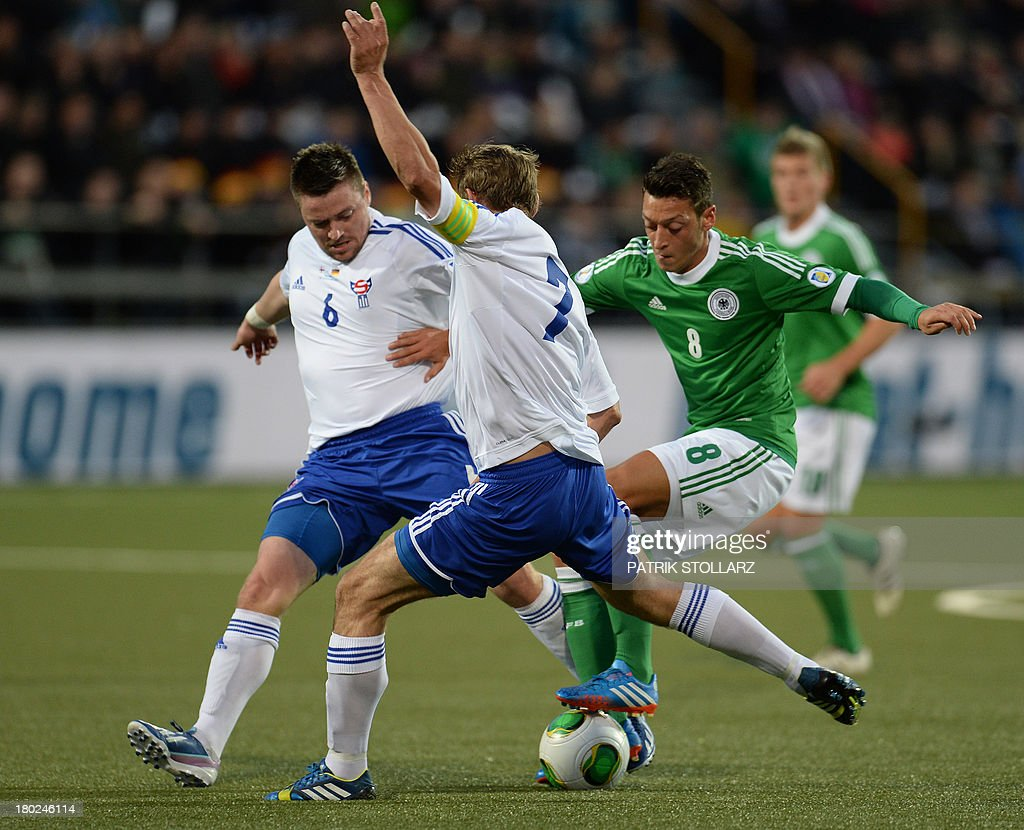 Germany's midfielder Mesut Oezil (R) vie for the ball Faroe Island's Frodi Benjaminsen and Suni Olsen (L) during the FIFA World Cup 2014 qualifying football match Faroe Island vs Germany in Torshavn on September 10, 2013. AFP PHOTO / PATRIK STOLLARZ