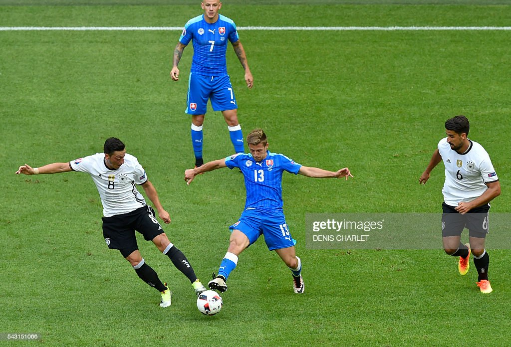 Germany's midfielder Mesut Oezil (L) vies with Slovakia's midfielder Patrik Hrosovsky during the Euro 2016 round of 16 football match between Germany and Slovakia at the Pierre-Mauroy stadium in Villeneuve-d'Ascq, near Lille, on June 26, 2016. / AFP / DENIS