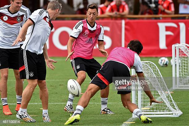 Germany's midfielder Mesut Ozil midfielder Bastian Schweinsteiger and Germany's midfielder Sami Khedira warm up with a rugby ball during a training...