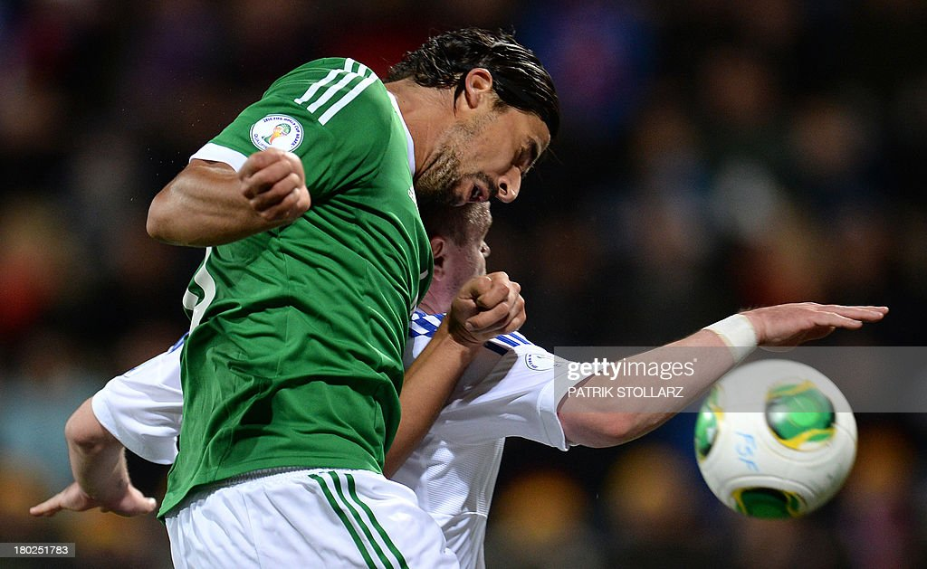 Germany's midfielder Sami Khedira (L) and Faroe Island's Frodi Benjaminsen vie for the ball during the FIFA World Cup 2014 qualifying football match Faroe Island vs Germany in Torshavn on September 10, 2013. AFP PHOTO / PATRIK STOLLARZ