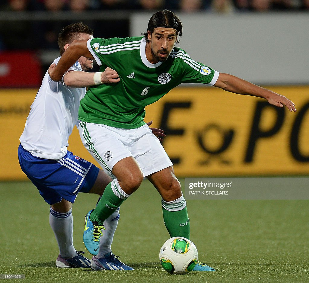 Germany's midfielder Sami Khedira and Faroe Island's Suni Olsen vie for the ball during the FIFA World Cup 2014 qualifying football match Faroe Island vs Germany in Torshavn on September 10, 2013.