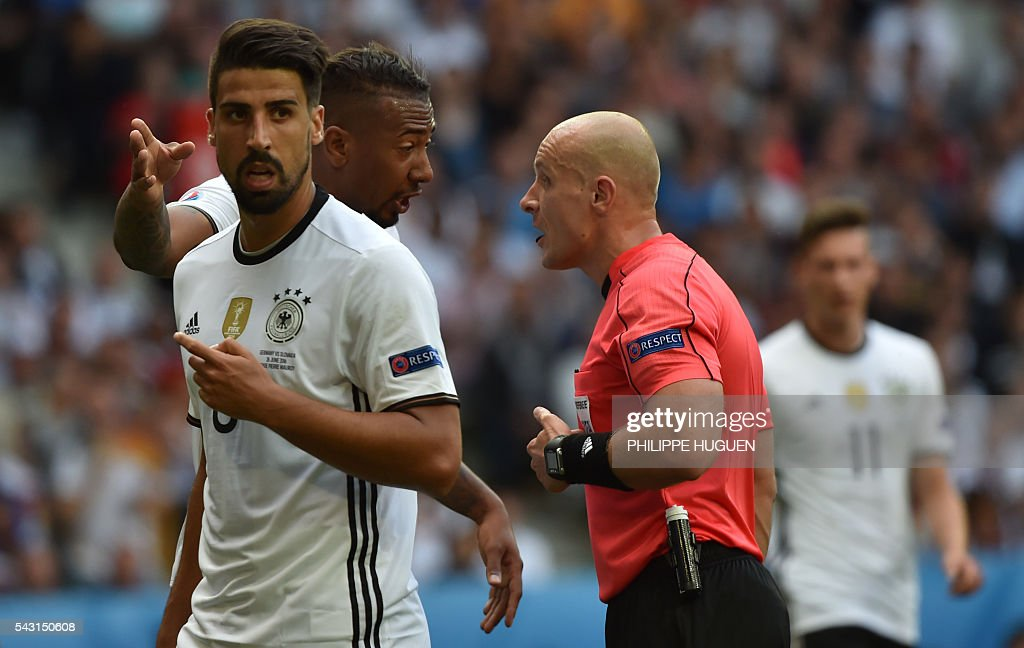 Germany's midfielder Sami Khedira and Germany's defender Jerome Boateng argue with Polish referee Szymon Marciniak during the Euro 2016 round of 16 football match between Germany and Slovakia at the Pierre-Mauroy stadium in Villeneuve-d'Ascq, near Lille, on June 26, 2016. / AFP / PHILIPPE