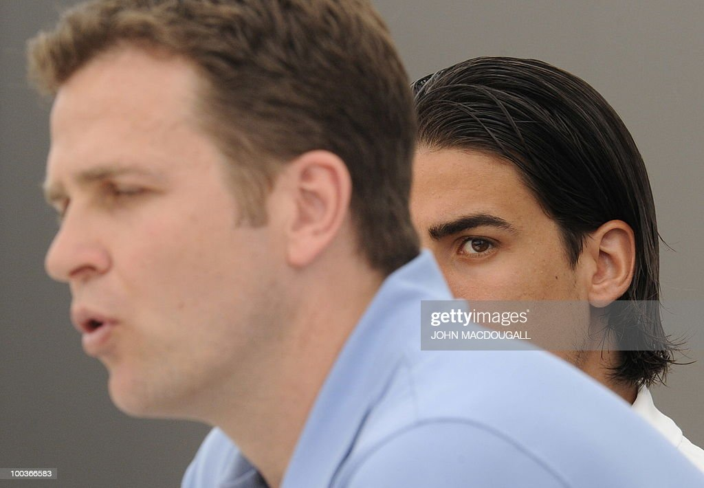 Germany's midfielder Sami Khedira (R) looks over Germany's team manager Oliver Bierhoff's shoulder during a press conference in Appiano, near the north Italian city of Bolzano May 24, 2010. The German football team is currently taking part in a 12-day training camp in Appiano to prepare for the upcoming FIFA Football World Cup in South Africa.