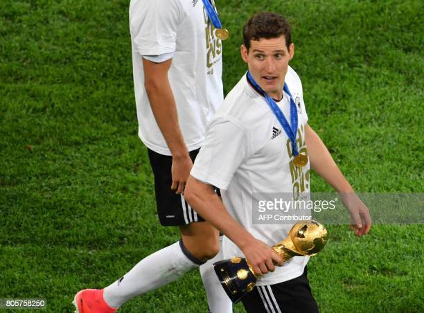 Germany's midfielder Sebastian Rudy holds the trophy after winning the 2017 Confederations Cup final football match between Chile and Germany at the...