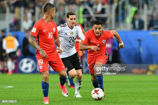 Germany's midfielder Sebastian Rudy vies for the ball against Chile's forward Leonardo Valencia and Chile's forward Alexis Sanchez during the 2017...