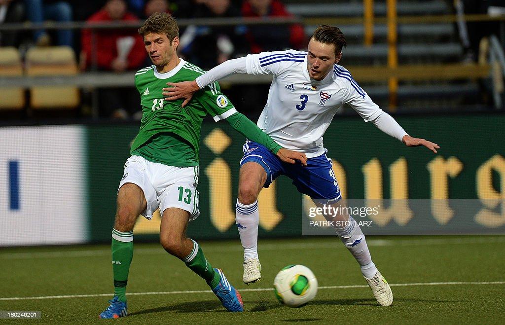 Germany's midfielder Thomas Mueller and Faroe Island's Viljomur Davidsen vie for the ball during the FIFA World Cup 2014 qualifying football match Faroe Island vs Germany in Torshavn on September 10, 2013.