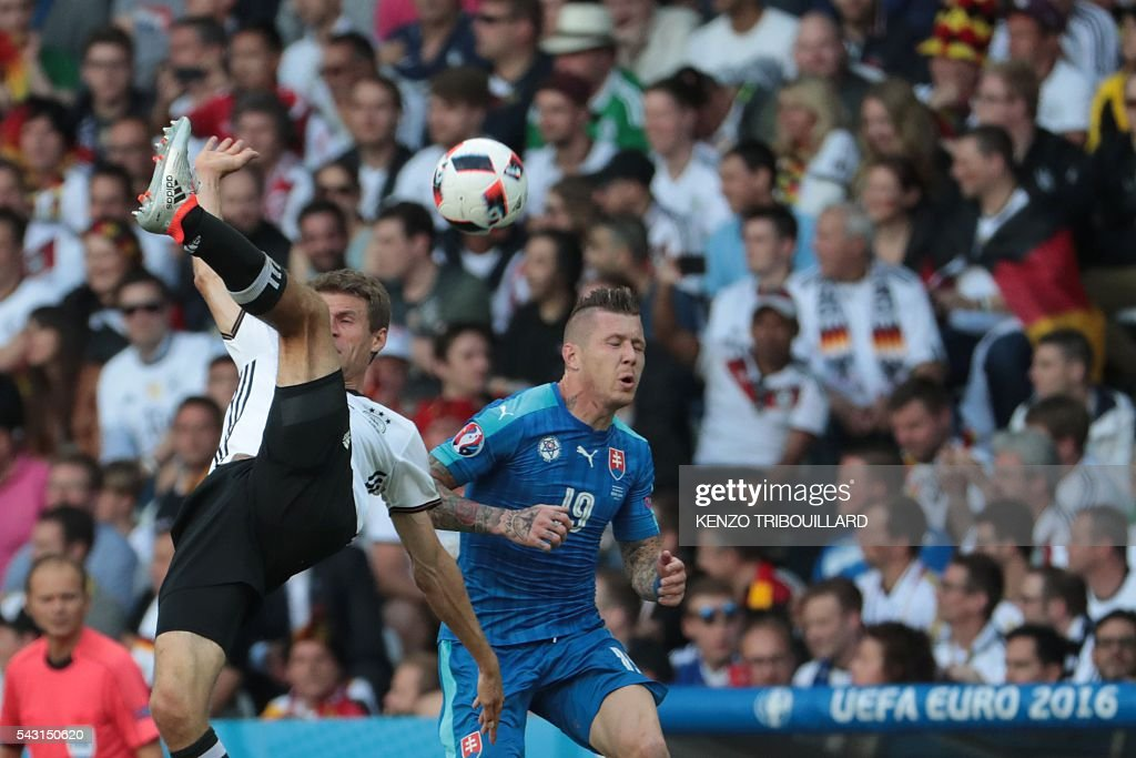 Germany's midfielder Thomas Mueller (L) challenges Slovakia's midfielder Juraj Kucka during the Euro 2016 round of 16 football match between Germany and Slovakia at the Pierre-Mauroy stadium in Villeneuve-d'Ascq near Lille on June 26, 2016. / AFP / KENZO