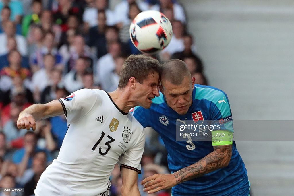 Germany's midfielder Thomas Mueller (R) heads the ball with Slovakia's defender Martin Skrtel during the Euro 2016 round of 16 football match between Germany and Slovakia at the Pierre-Mauroy stadium in Villeneuve-d'Ascq near Lille on June 26, 2016. / AFP / KENZO