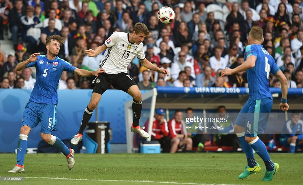 Germany's midfielder Thomas Mueller (C) jumps for the ball next to Slovakia's defender Norbert Gyomber (L) and Slovakia's defender Jan Durica during the Euro 2016 round of 16 football match between Germany and Slovakia at the Pierre-Mauroy stadium in Villeneuve-d'Ascq, near Lille, on June 26, 2016. / AFP / PHILIPPE