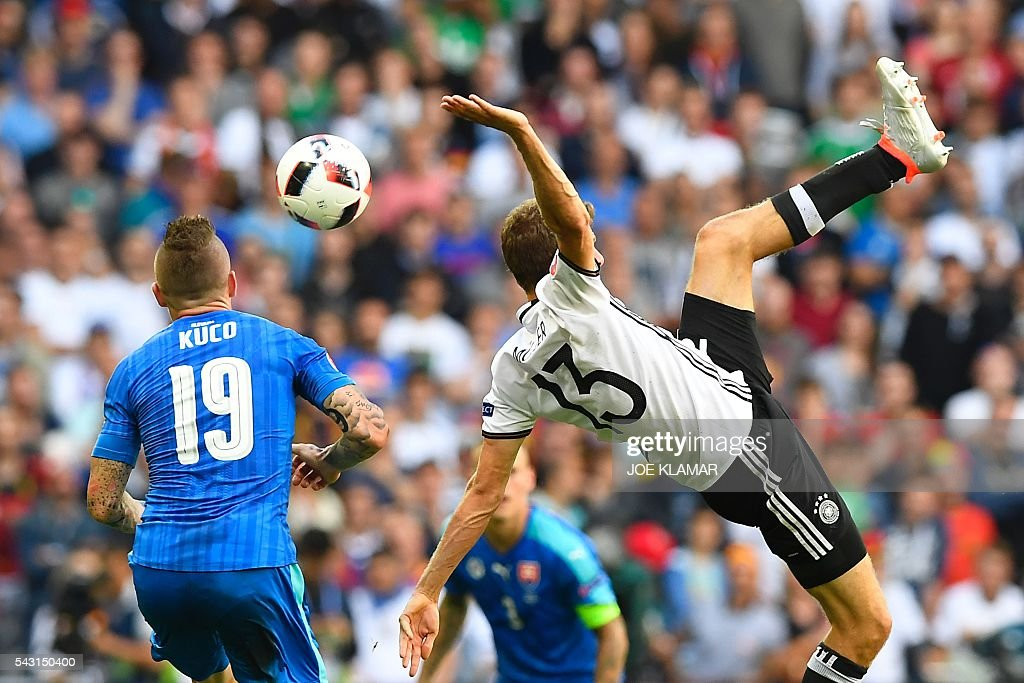 Germany's midfielder Thomas Mueller (R) jumps for the ball next to Slovakia's midfielder Juraj Kucka during the Euro 2016 round of 16 football match between Germany and Slovakia at the Pierre-Mauroy stadium in Villeneuve-d'Ascq near Lille on June 26, 2016. / AFP / Joe KLAMAR