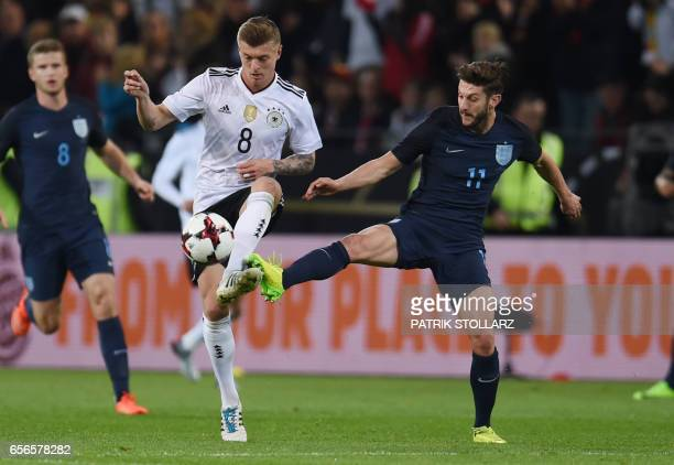 Germany's midfielder Toni Kroos and England´s Adam Lallana vie during a friendly football match between Germany and England on March 22 2017 in...