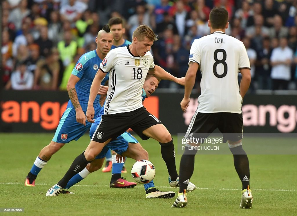 Germany's midfielder Toni Kroos (C) controls the ball during the Euro 2016 round of 16 football match between Germany and Slovakia at the Pierre-Mauroy stadium in Villeneuve-d'Ascq, near Lille, on June 26, 2016. / AFP / PHILIPPE