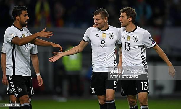 Germany's midfielder Toni Kroos is congratulated by Germany's midfielder Sami Khedira and Germany's midfielder Thomas Mueller after scoring the 20...