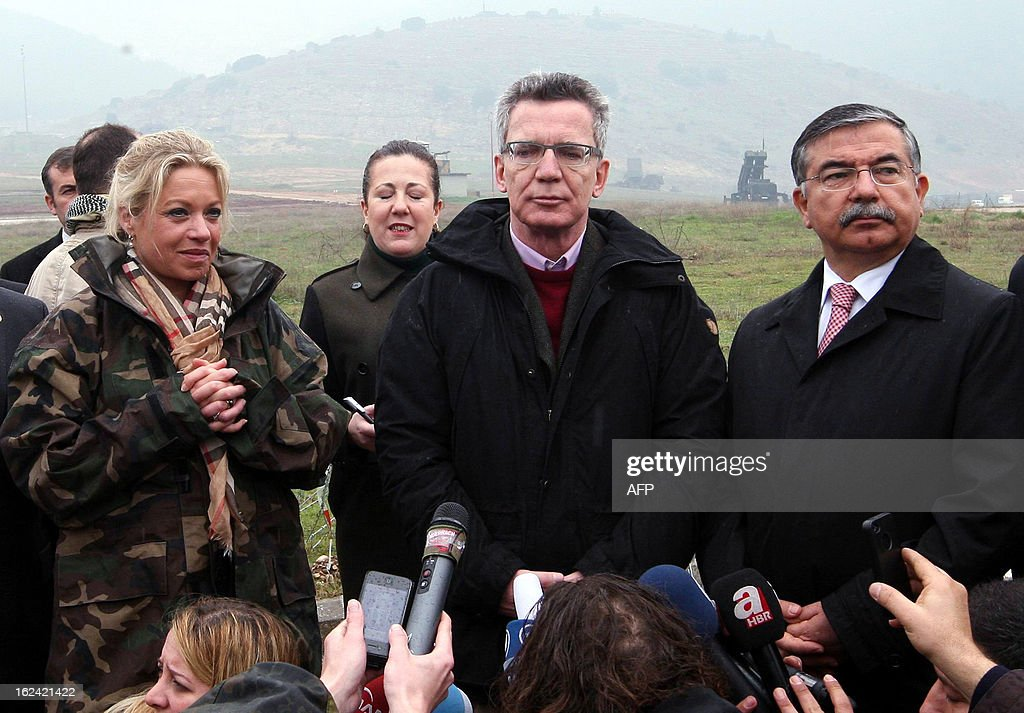 Germany's Minister of Defense Thomas de Maiziere (C), flanked by his counterparts Jeanine Hennis-Plasschaert of the Netherlands (L) and Ismet Yilmaz of Turkey (R), speaks during a visit to NATO German patriot troops at a Turkish military base in Kahramanmaras on February 23, 2013.