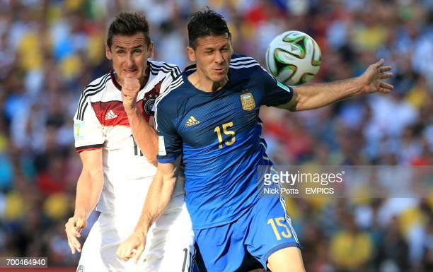 Germany's Miroslav Klose and Argentina's Martin Demichelis battle for the ball