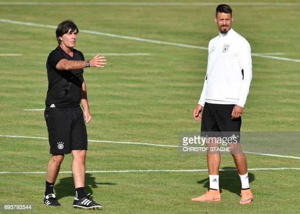 Germany's national football coach Joachim Loew gestures beside of Germany's midfielder Sandro Wagner during a trainings session in Herzogenaurach...