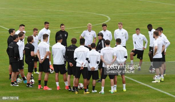 Germany's national football coach Joachim Loew speaks with players prior a training session in Herzogenaurach southern Germany on June 9 2017 on the...
